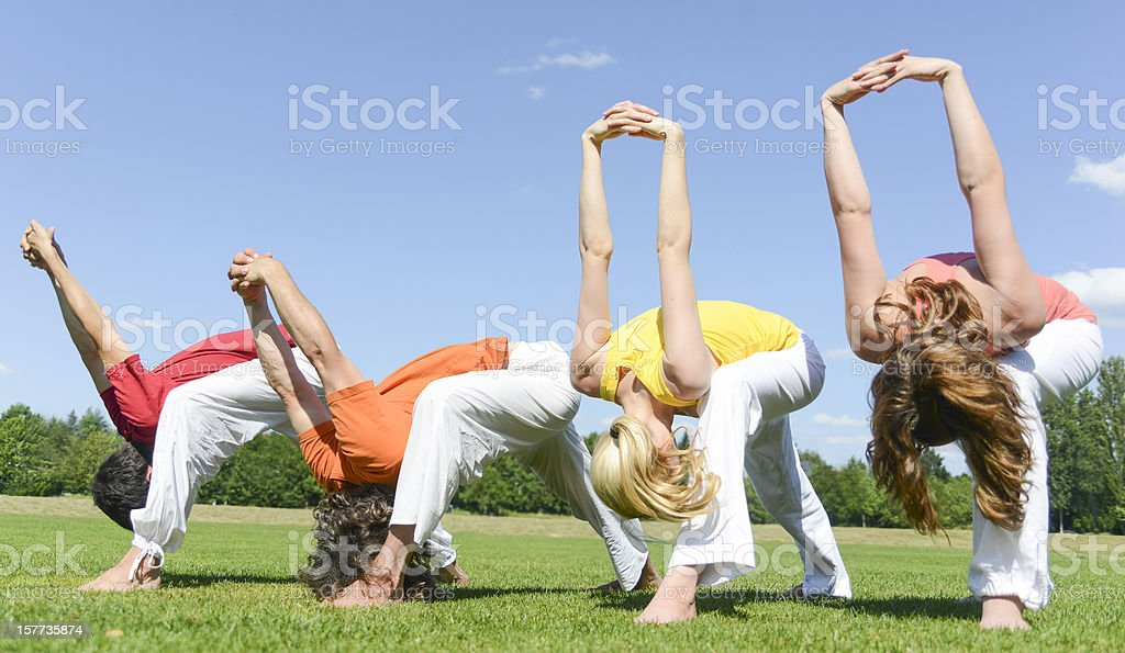 yoga group outside on meadow with four people stretching aerobic stock photo