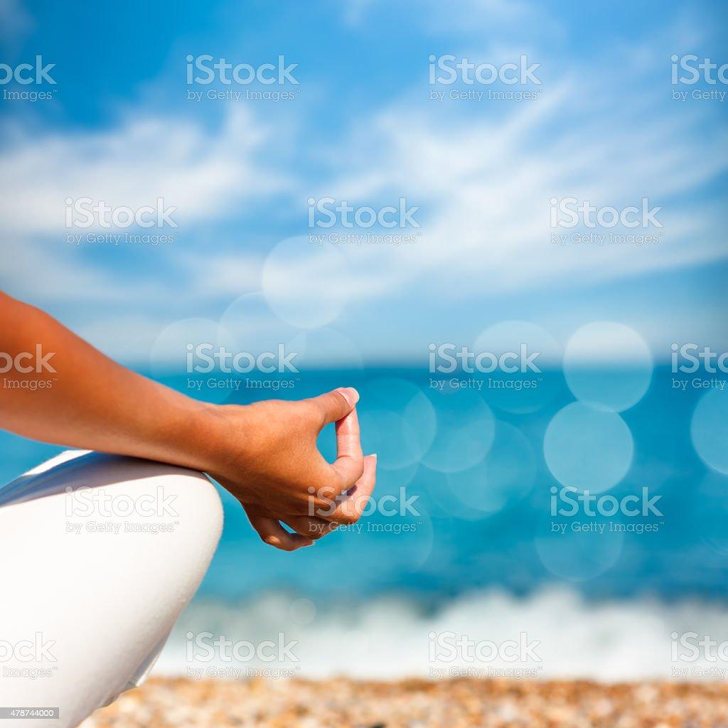 Yoga Hand on Sea Background stock photo