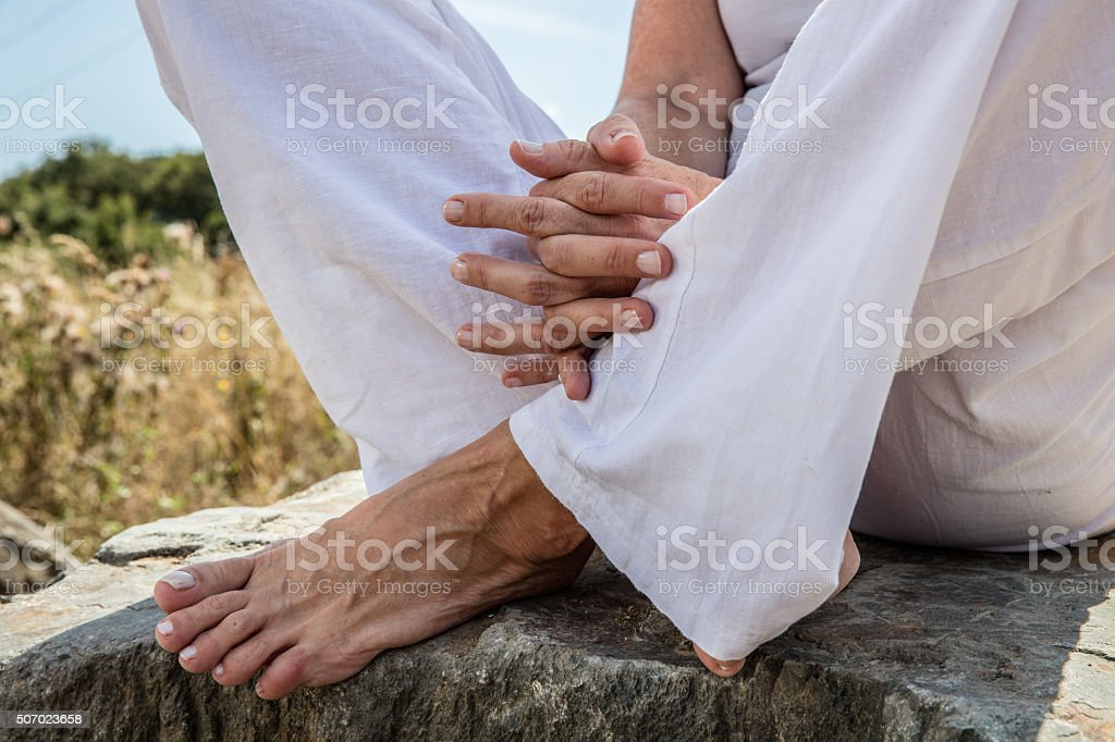 yoga hands and bare feet of woman in lotus position stock photo