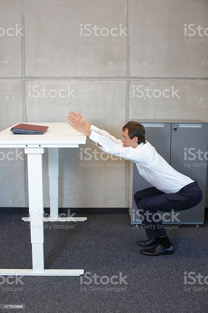 yoga in office. business man exercising at workplace stock photo