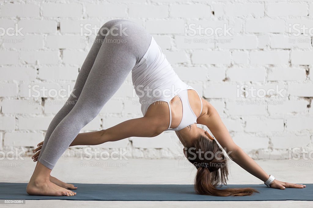 Yoga Indoors: Revolved Downward-facing dog pose stock photo