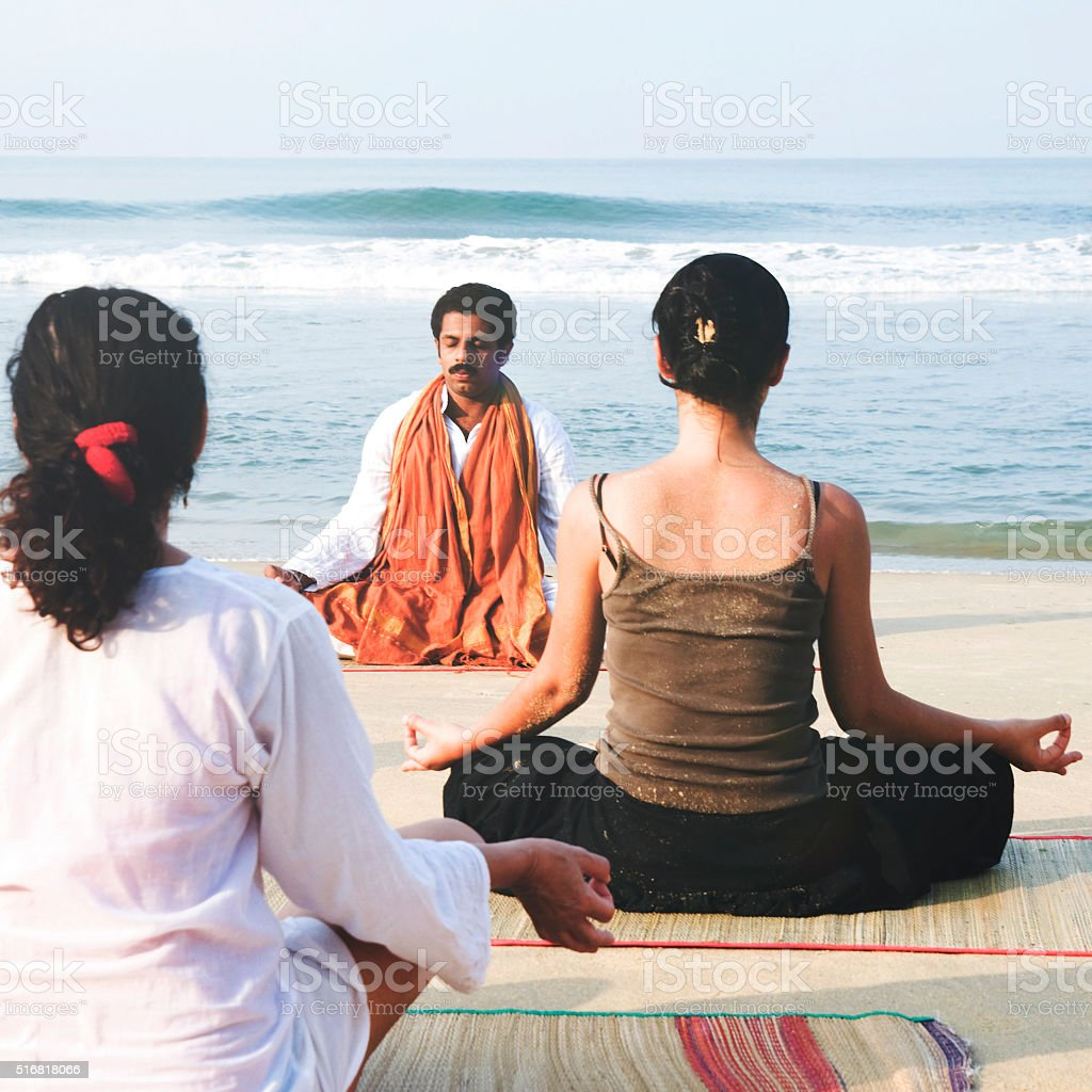 Yoga Instructor And His Students By The Beach Concept stock photo