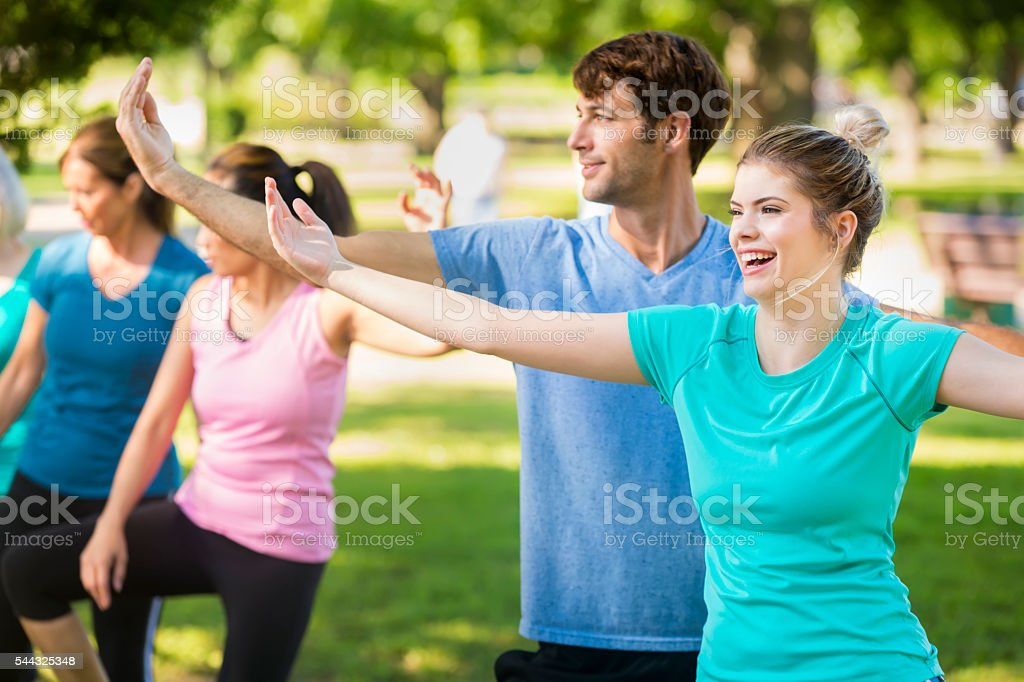 Yoga instructor and young woman in park working out stock photo