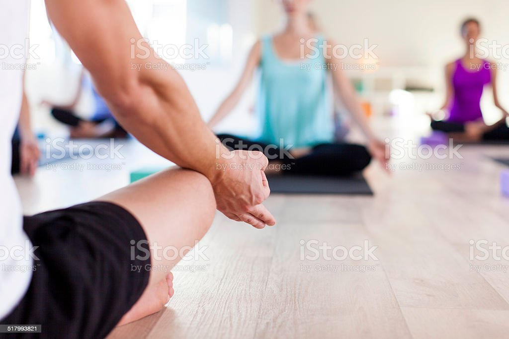 Yoga instructor showing his learners what to do stock photo