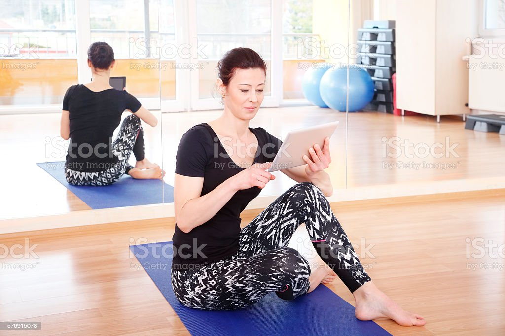 Yoga instructor with digital tablet stock photo