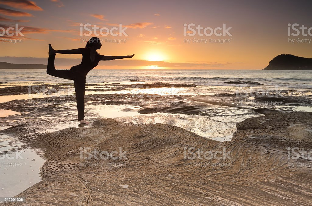 Yoga King Dancer Pose balance by the sea stock photo