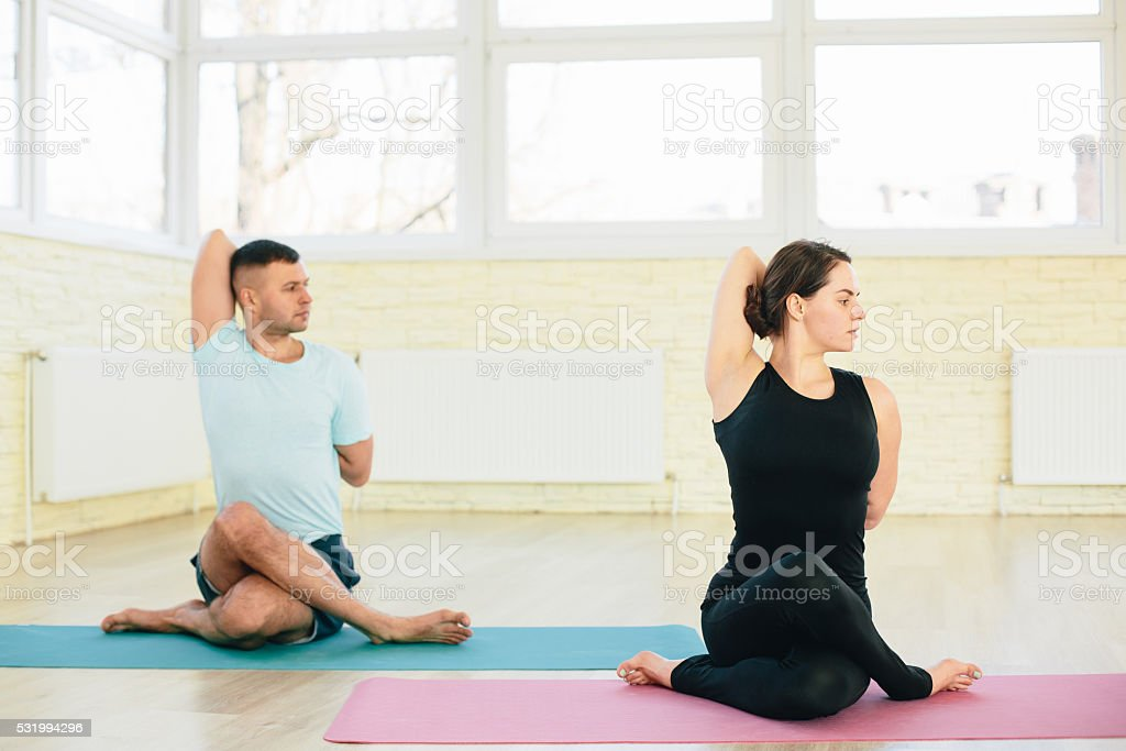 yoga man and woman, practice exercises in a training hall stock photo