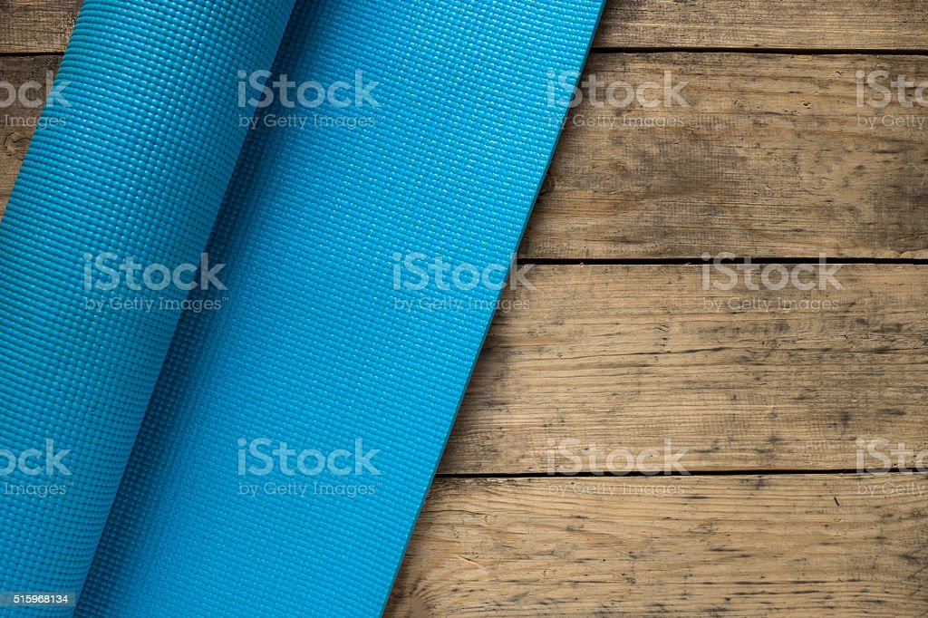 Yoga mat on old wood table stock photo