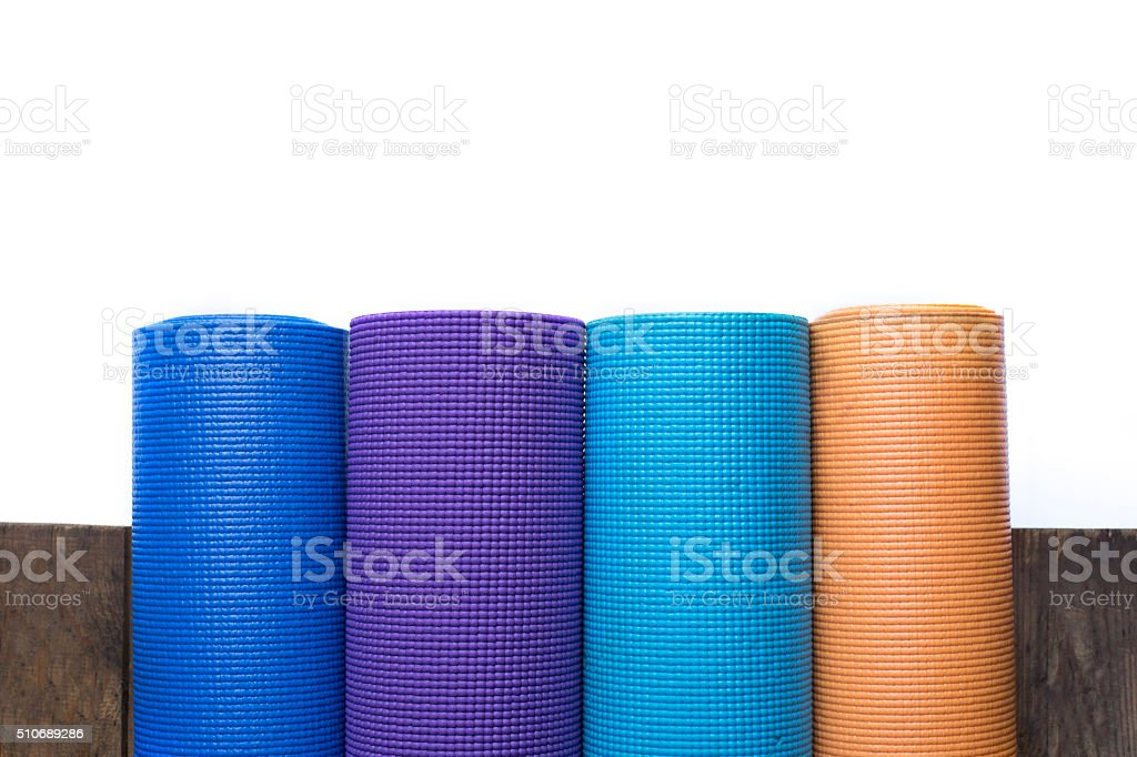 Yoga mats on the wood table and white background stock photo