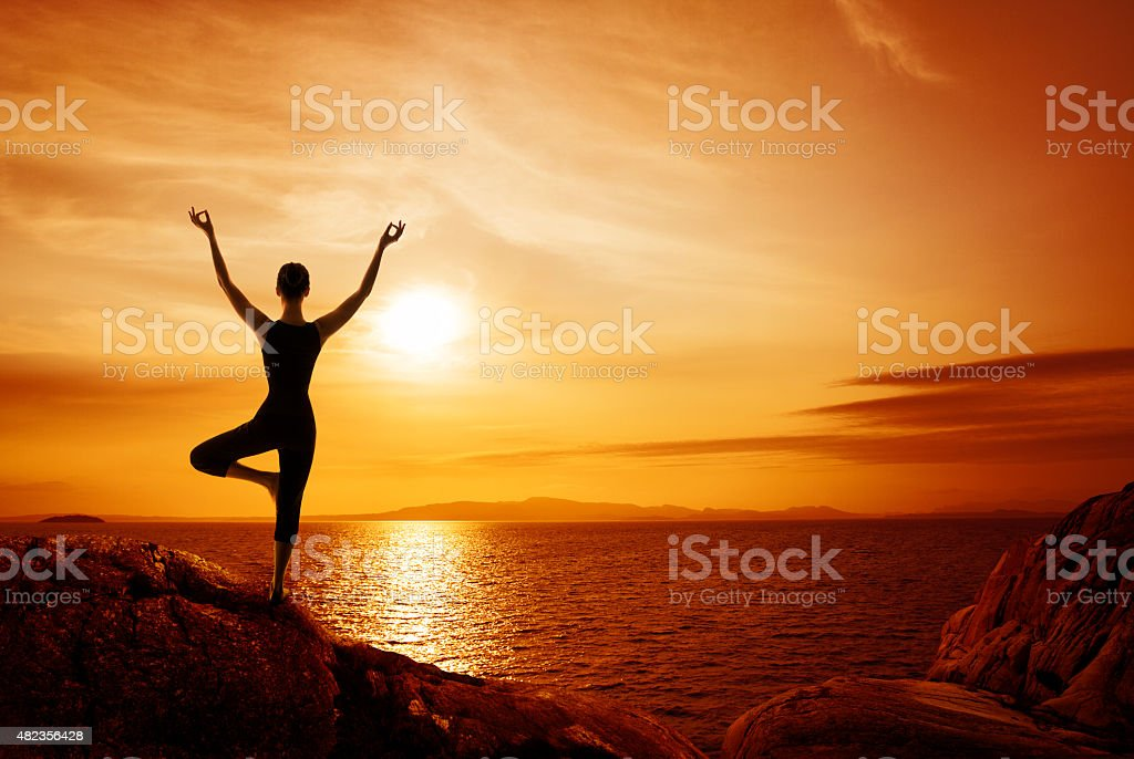 Yoga Meditation Concept, Woman Silhouette Meditating in Nature, sunset sea stock photo