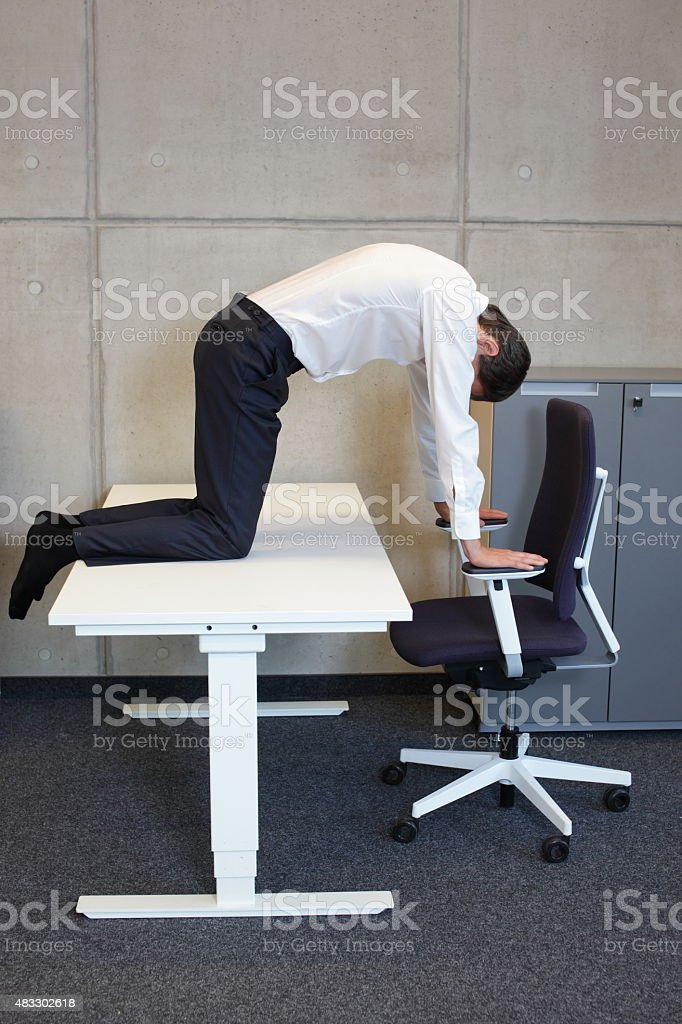 yoga office - man practicing at workplace stock photo
