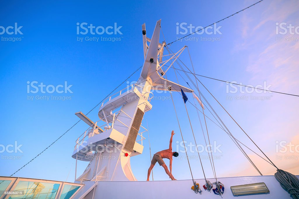 Yoga on ship in the  morning - utthita trikonasana stock photo