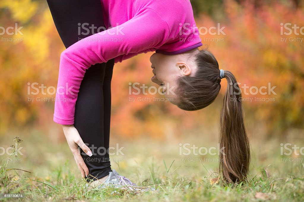 Yoga outdoors: Standing forward bend pose stock photo