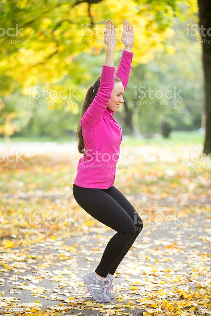 Yoga outdoors: Utkatasana posture stock photo