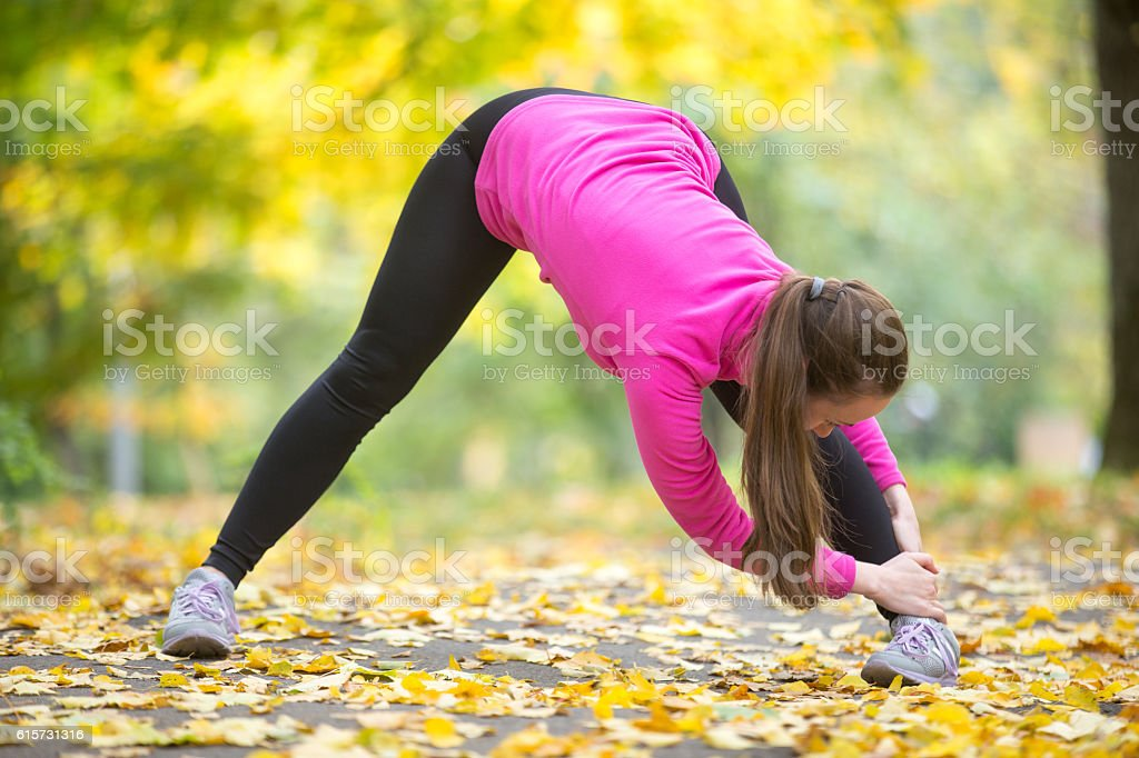 Yoga outdoors: Wide Legged Forward Bend Pose stock photo