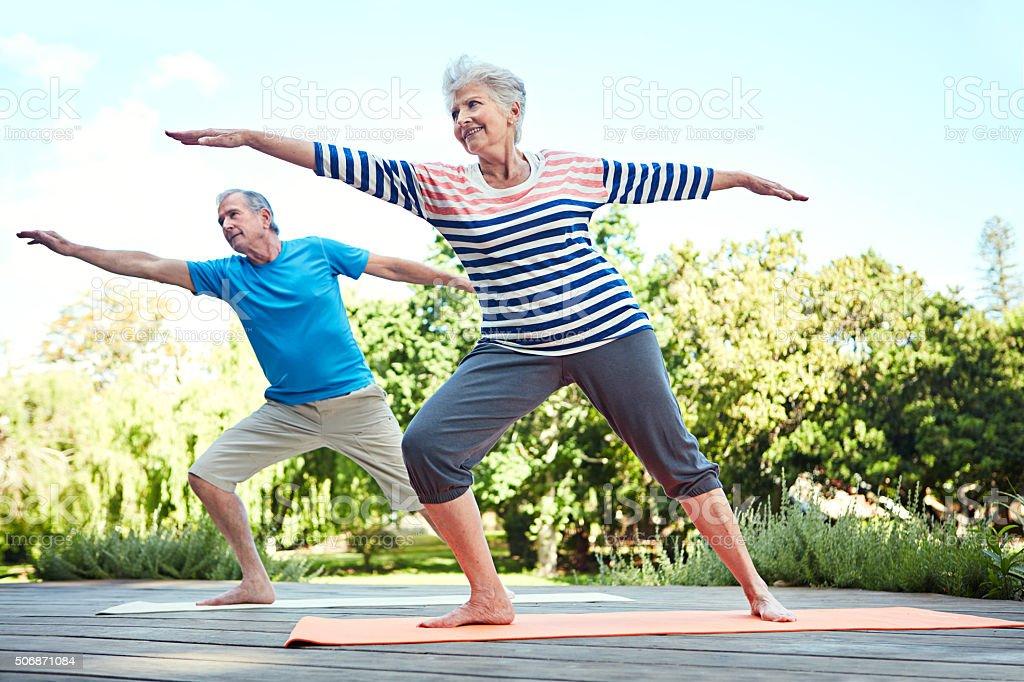 Shot of a senior couple doing yoga together...