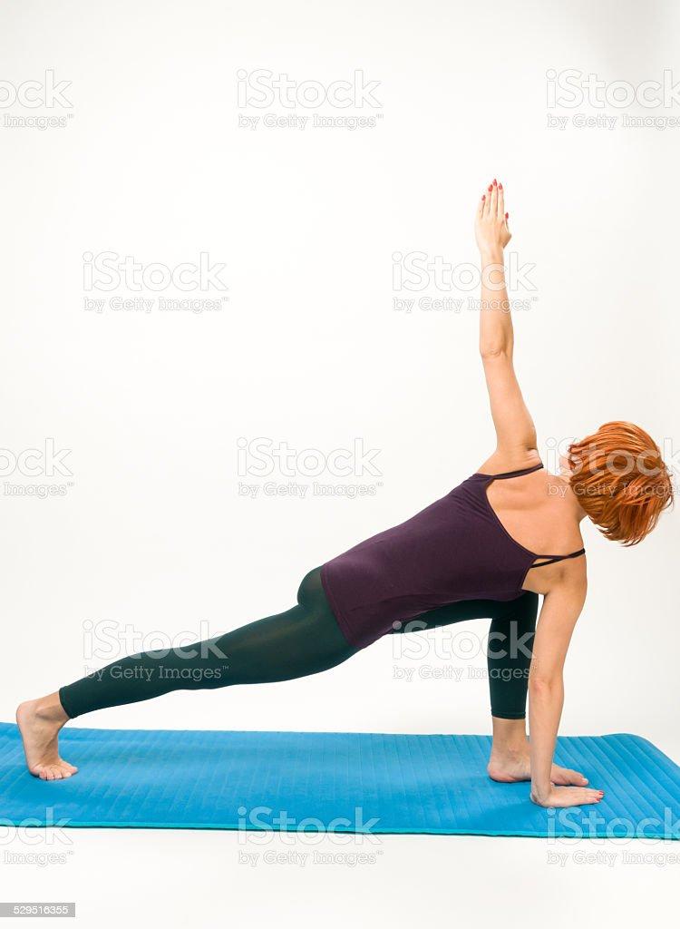 Yoga posing on a gray studio background stock photo