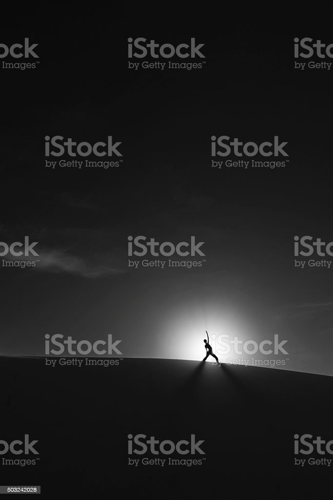 Yoga posing silhouette on a sand dune royalty-free stock photo