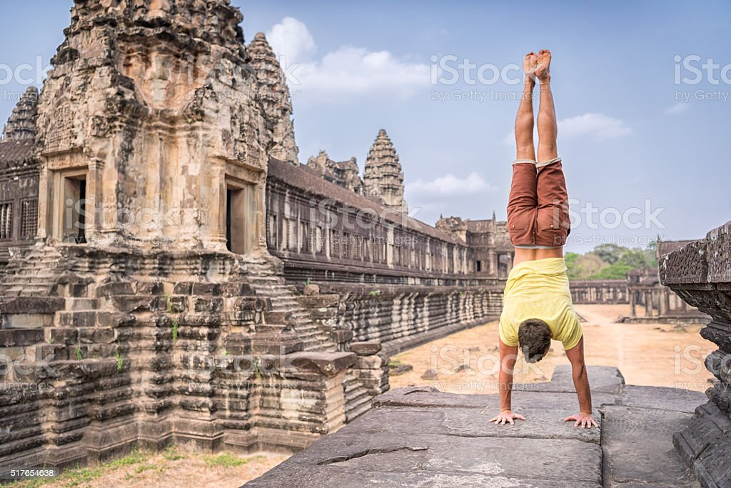 Yoga Retreat, Handsome man doing a Handstand, Angkor Wat stock photo