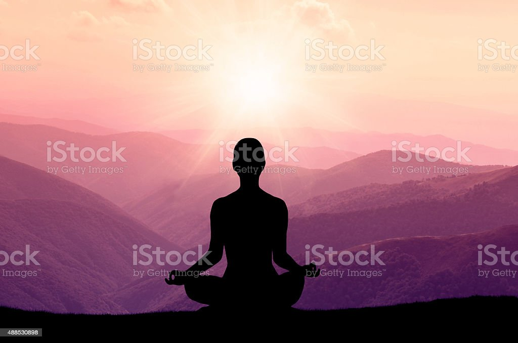 Yoga silhouette on the mountain in sunrays stock photo