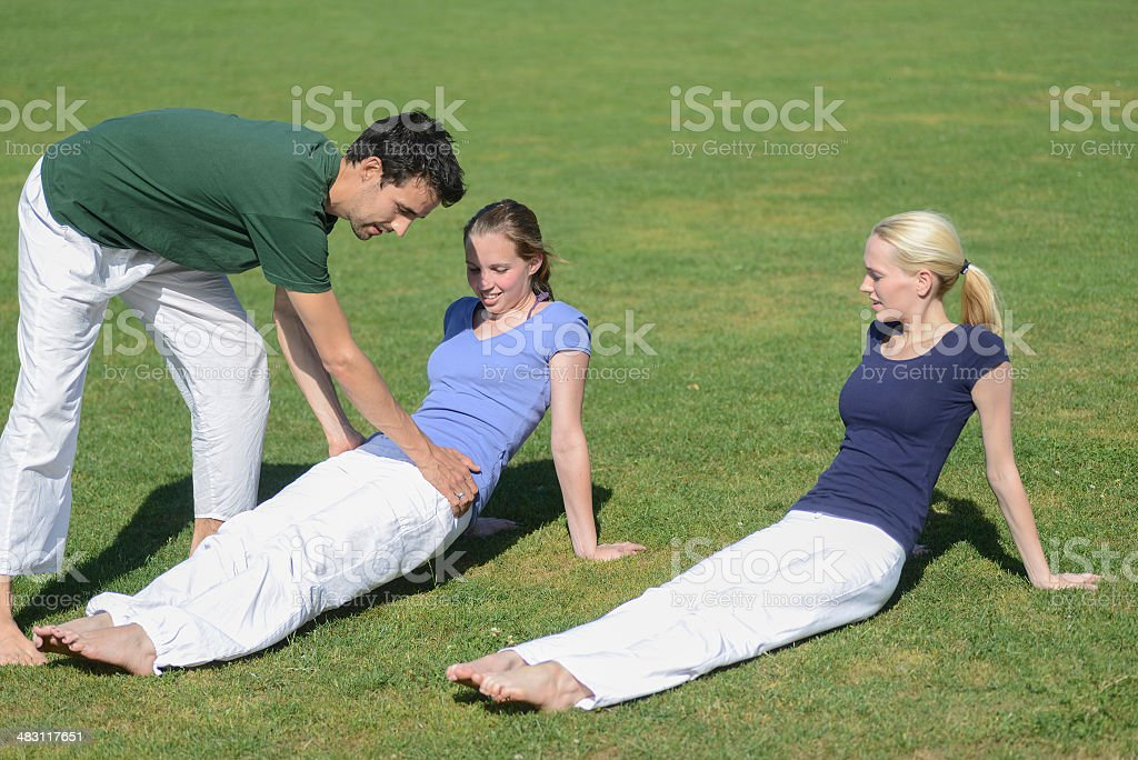 Yoga teacher outdoor helping two girls on meadow royalty-free stock photo