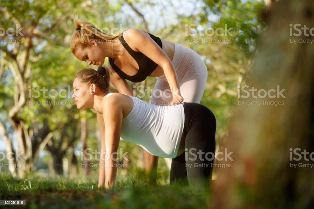 Yoga Trainer Helping Pregnant Woman With Exercise For Backpain stock photo