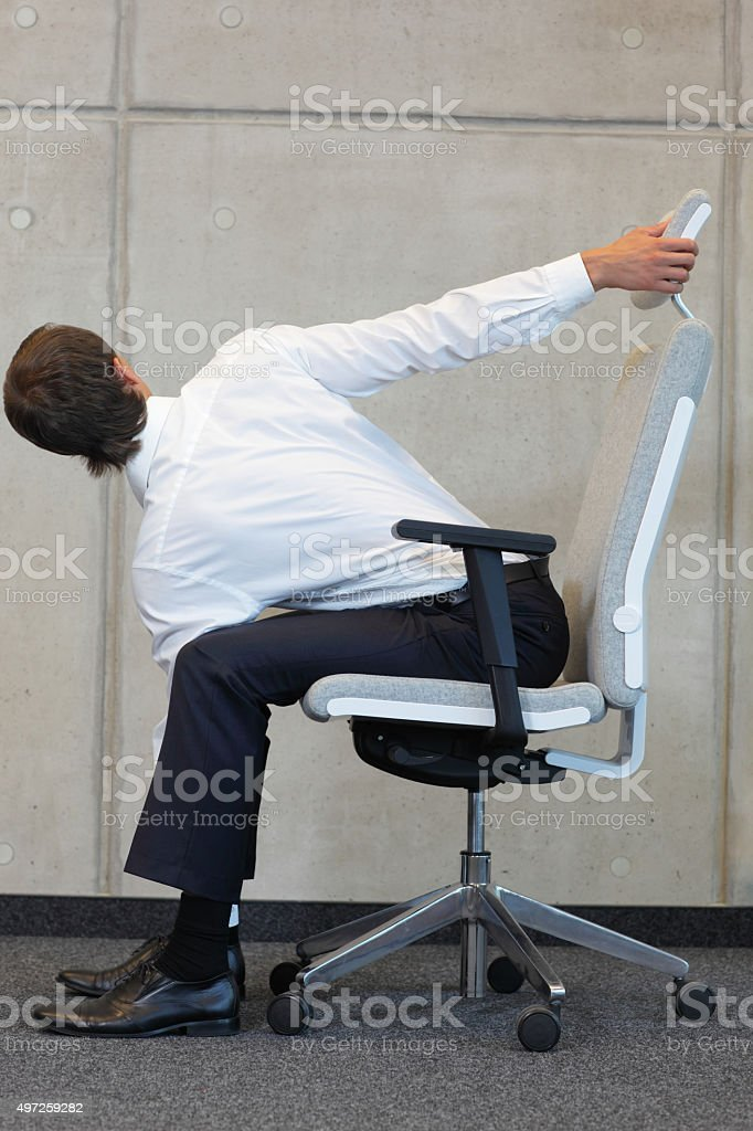 yoga with chair in office - business man exercising in office