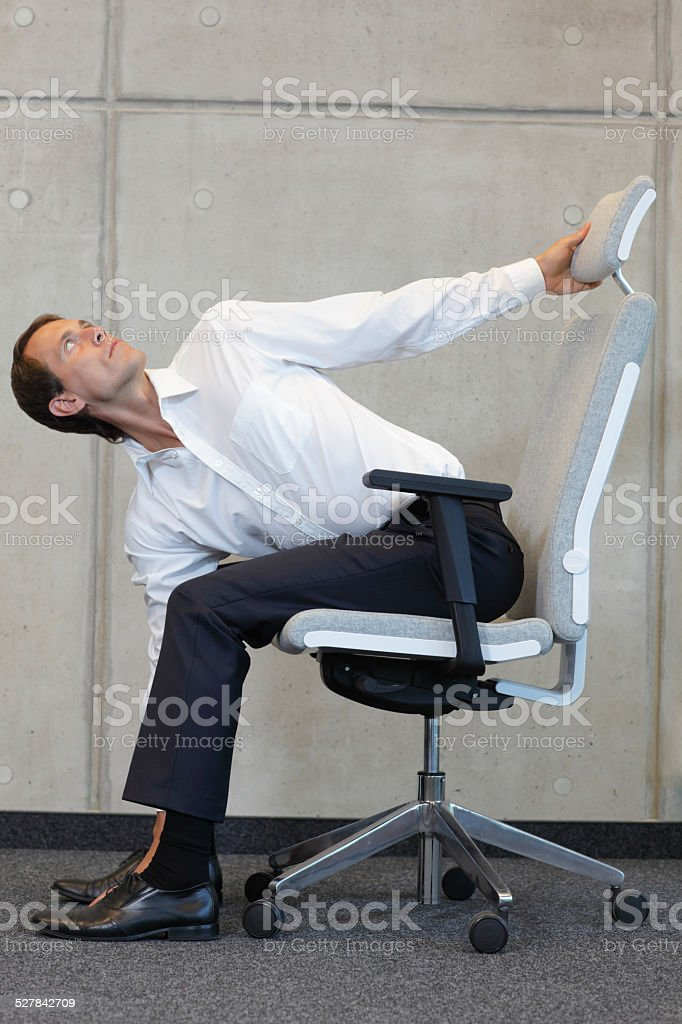 yoga with chair in office business man exercising in office stock