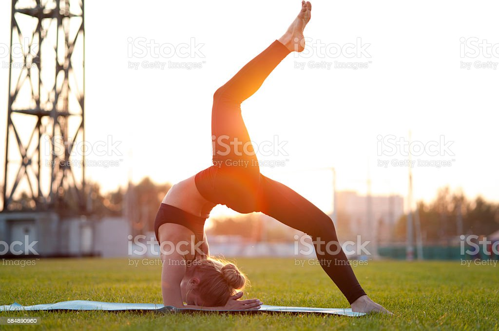 Yoga woman exercising on green grass outdoors stock photo