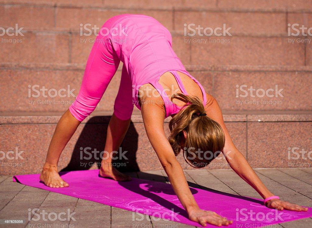 Yoga woman in Downward Facing Dog Position (Adho Mukha Svanasana) stock photo