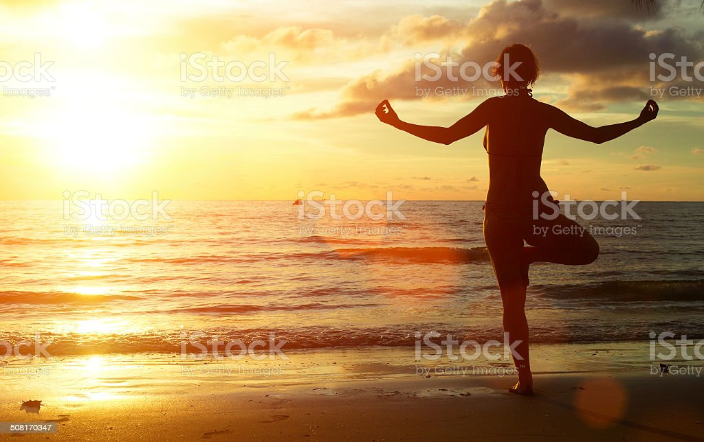 Yoga woman on the beach during sunset. stock photo