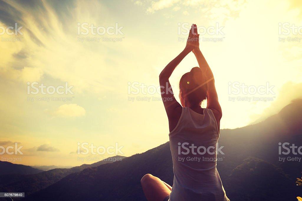 yoga woman practice on mountain peak stock photo