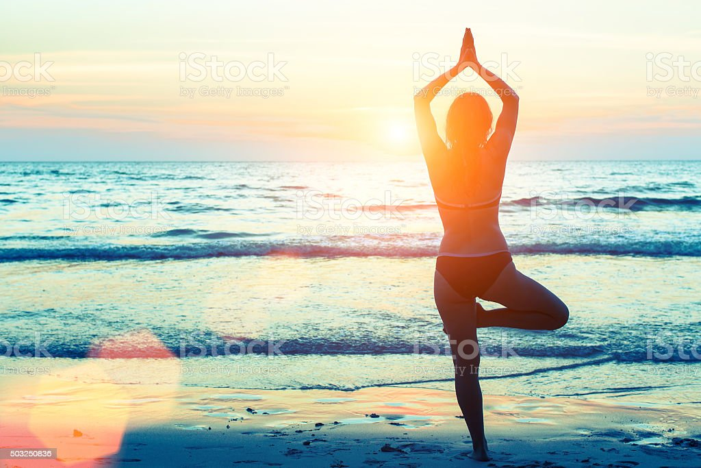 Yoga woman silhouette. Woman doing meditation near the ocean. stock photo
