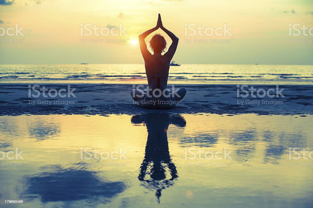 Yoga woman sitting in lotus pose on the beach stock photo