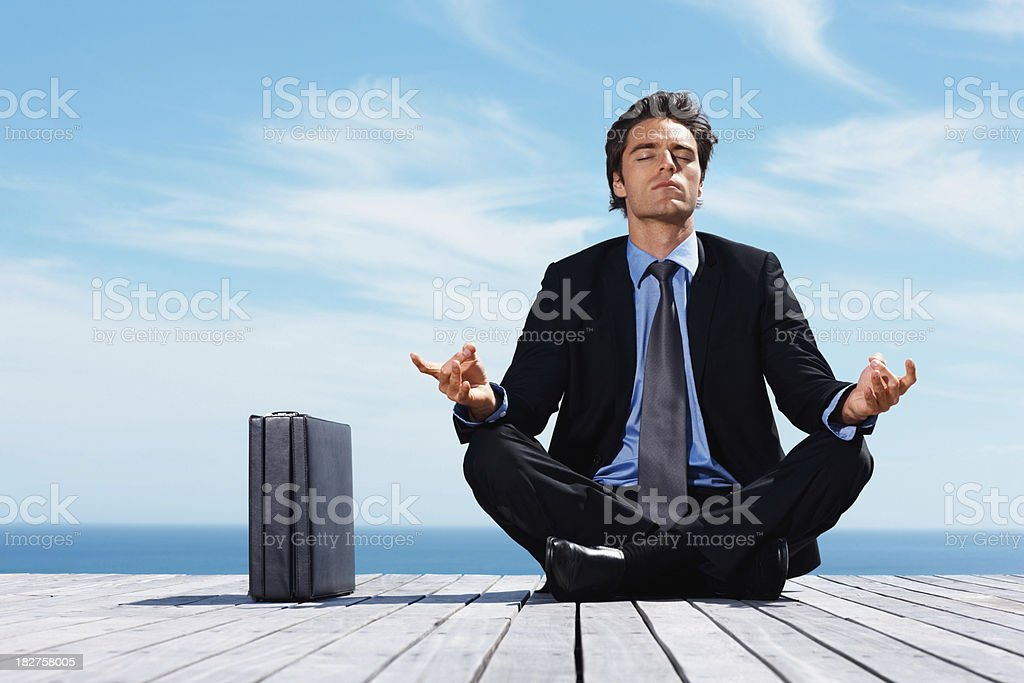 Yoga - Young man in cross-legged position sitting on jetty royalty-free stock photo