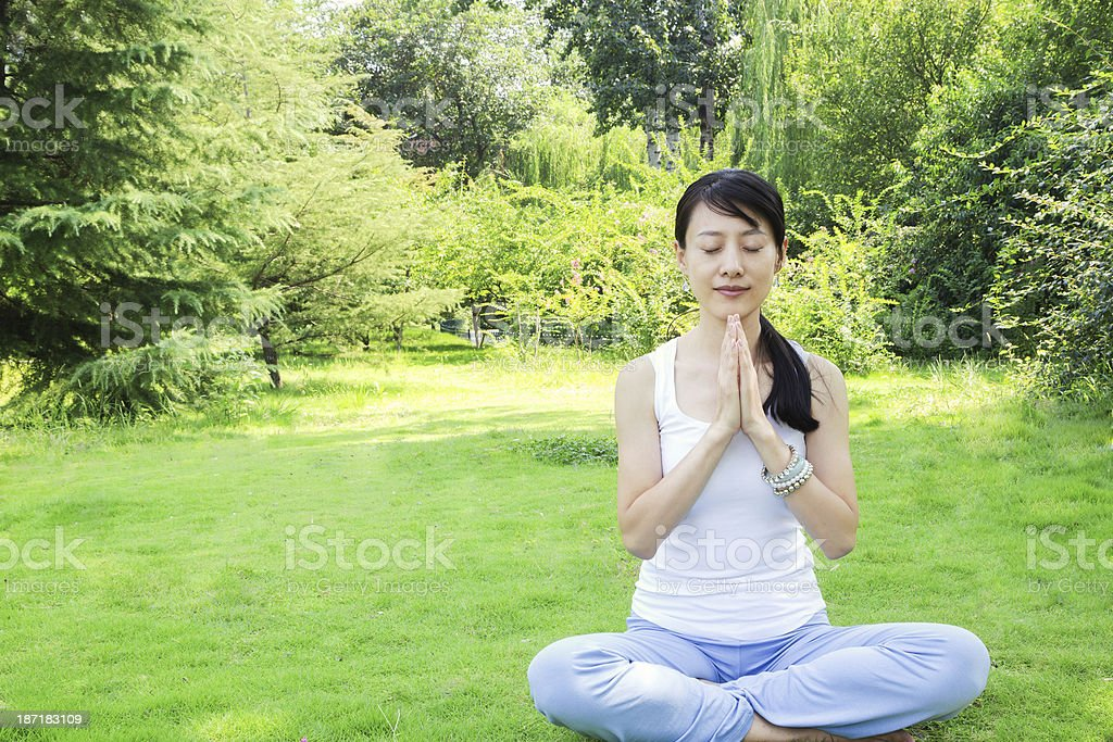 Yoga:Asian young woman meditation on grass royalty-free stock photo