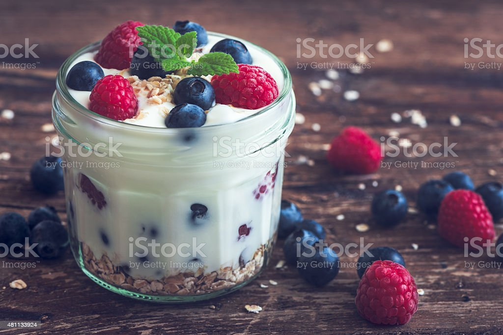 Yoghurt with Fresh Berries on Woden Table stock photo