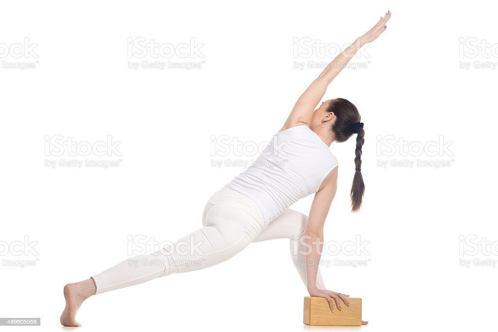 Yogi female exercising with wood brick stock photo