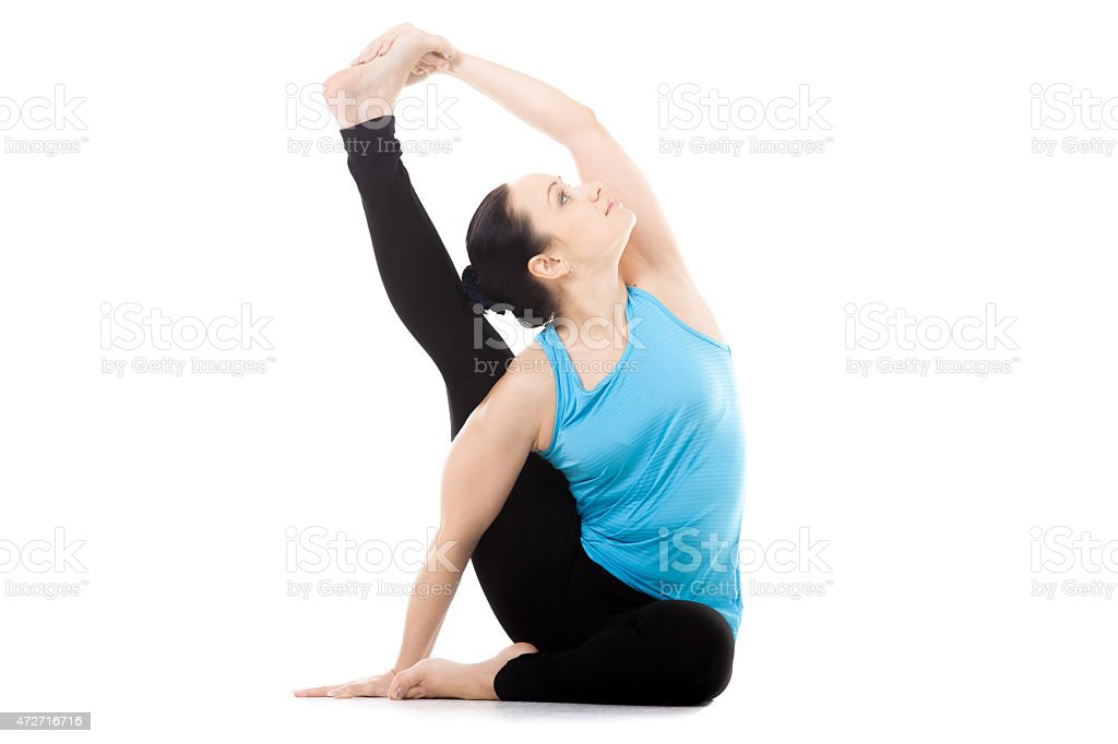 Yogi female in yoga asana Parivritta Surya Yantrasana stock photo