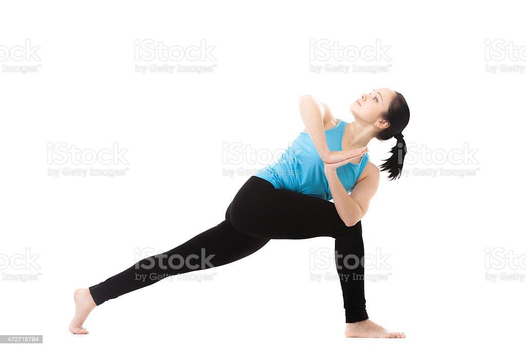 Yogi female in yoga Pose parivritta parshvakonasana stock photo