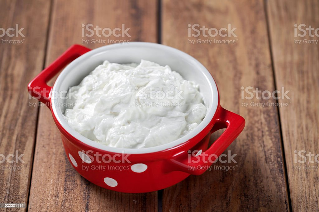 Yogurt in porcelain bowl on wooden table stock photo