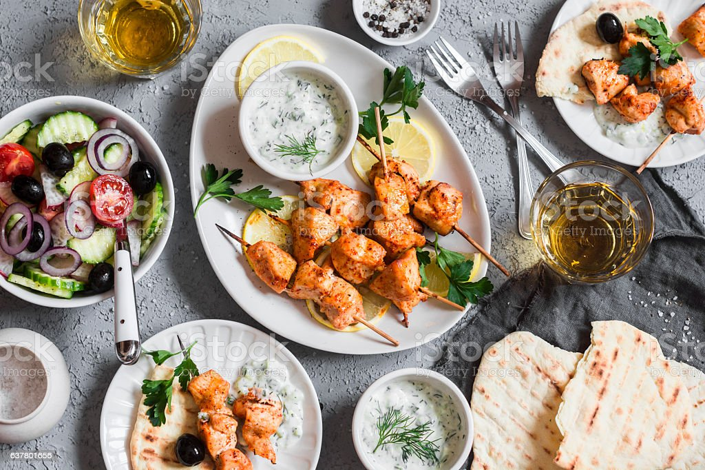 Yogurt marinated grilled chicken skewers with vegetables and tzatziki stock photo