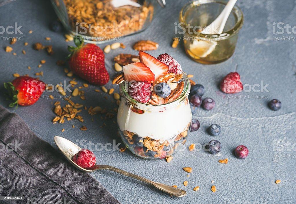 Yogurt oat granola with fresh berries, nuts, honey and mint stock photo