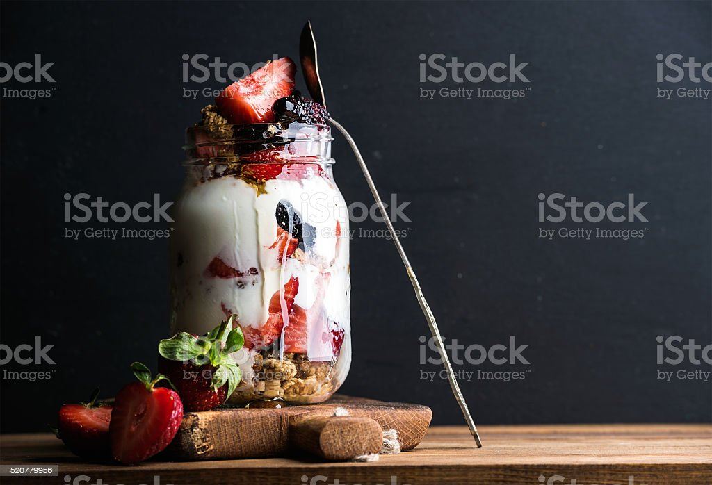 Yogurt oat granola with strawberries, mulberries, honey and mint leaves stock photo