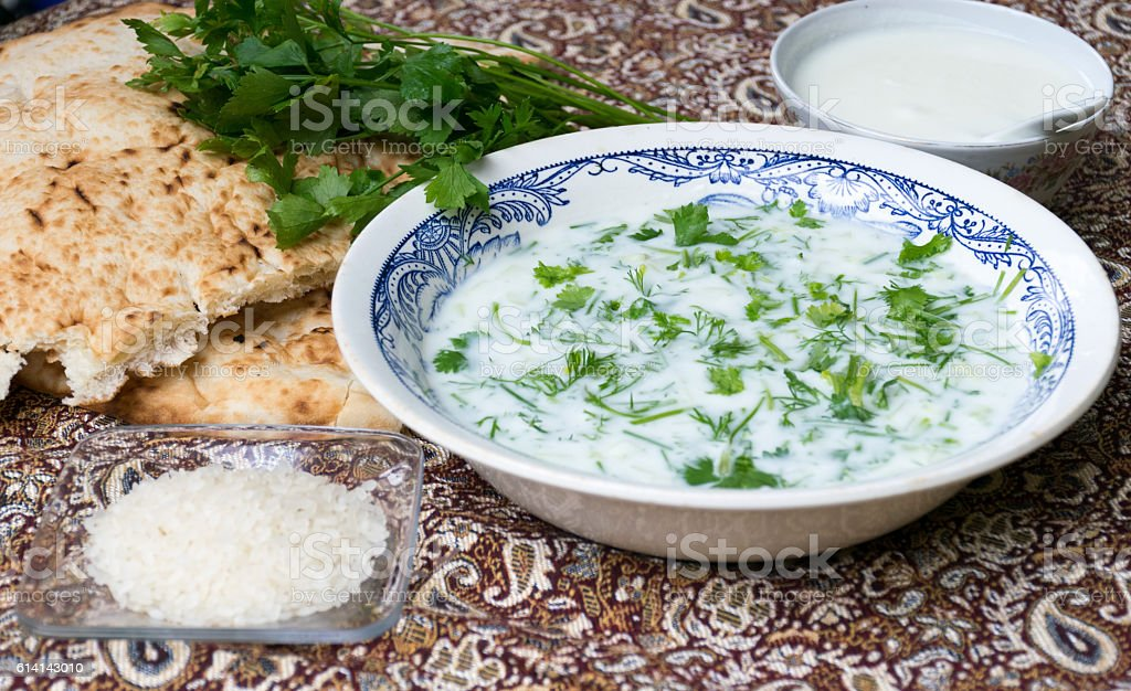 Yogurt soup with fresh herbs, rice, and bread stock photo