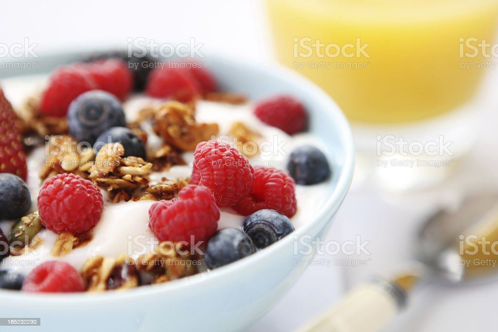 Yogurt with fresh berries and granola served in a white bowl royalty-free stock photo