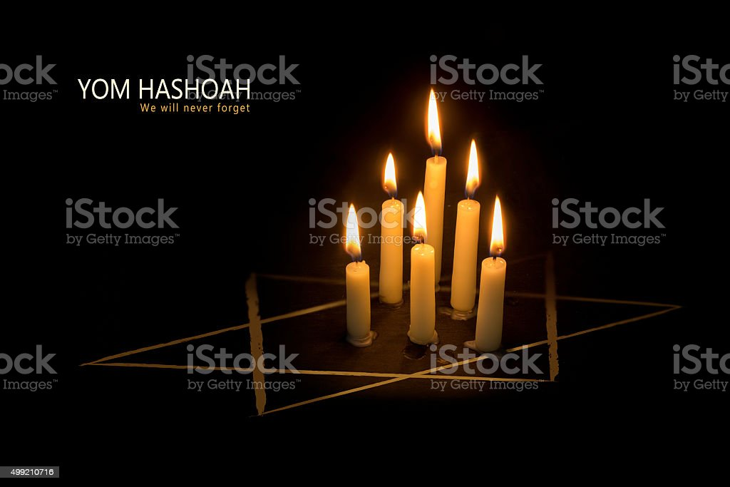 Yom Hashoah, candles and the star of David on black stock photo