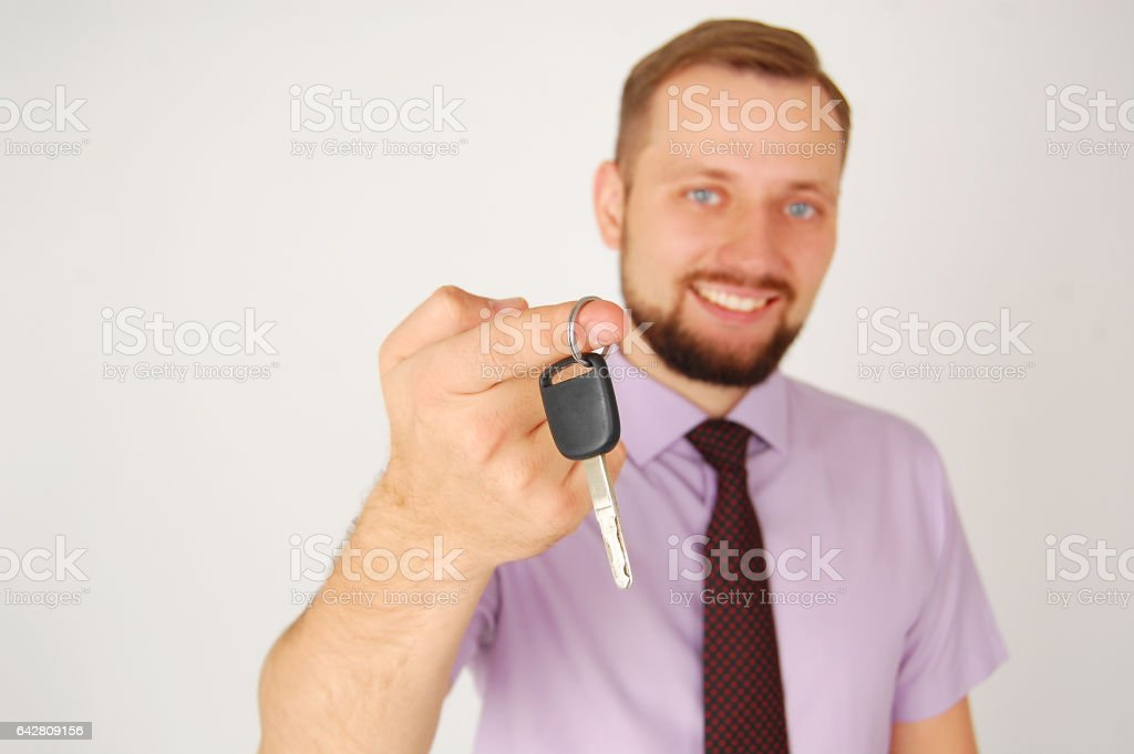 Yong guy in shirt and tie gives to you key from car stock photo