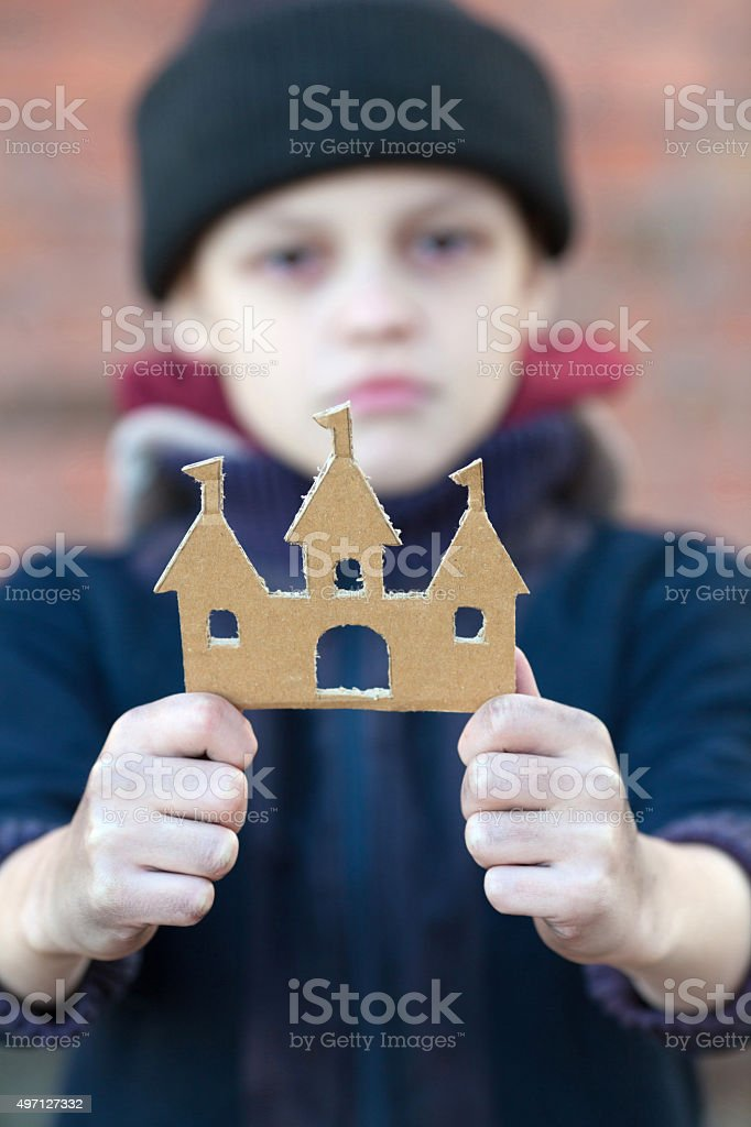 yong homeless boy holds a cardboard castle stock photo
