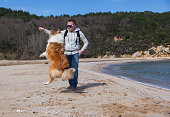 Yong man teaching rough collie dog to jump
